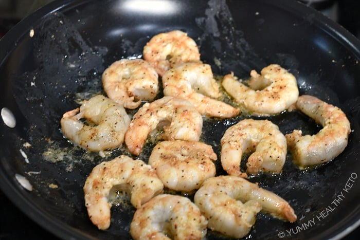 Seasoned shrimp cooking in a non-stick skillet.