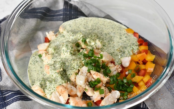 Shrimp, bell pepper, green onions and cilantro lime dressing in a glass mixing bowl.