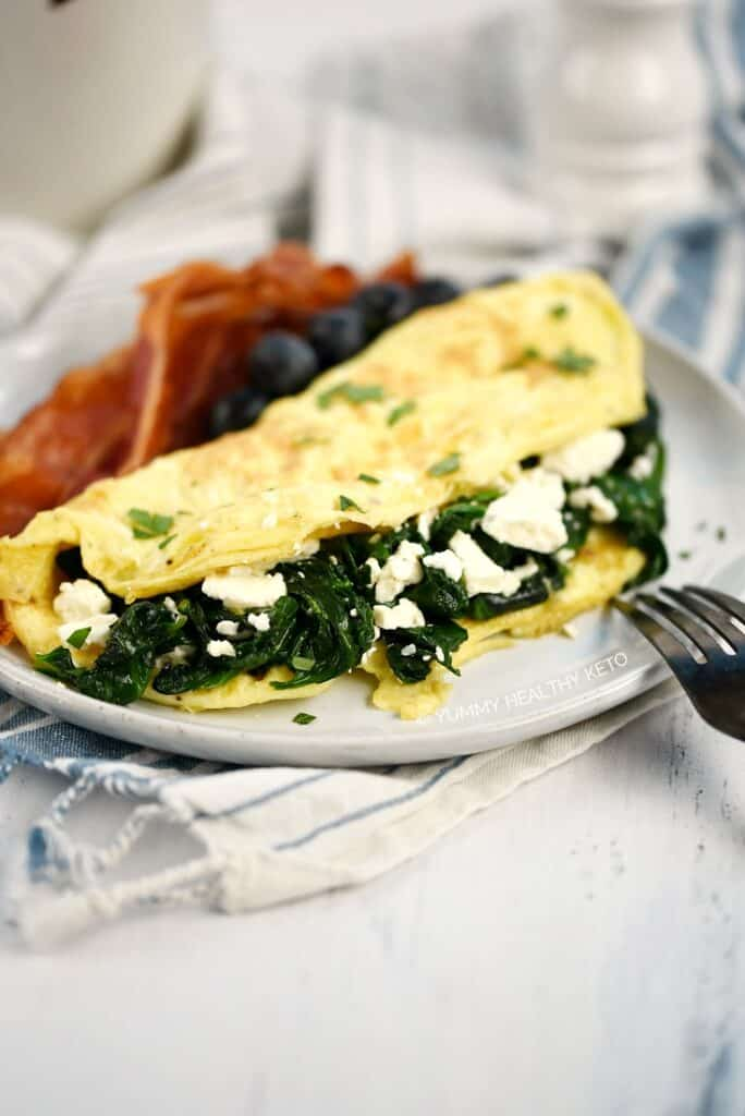 A close up image of a Spinach and Feta Omelette on a small plate with bacon slices and fresh blueberries.