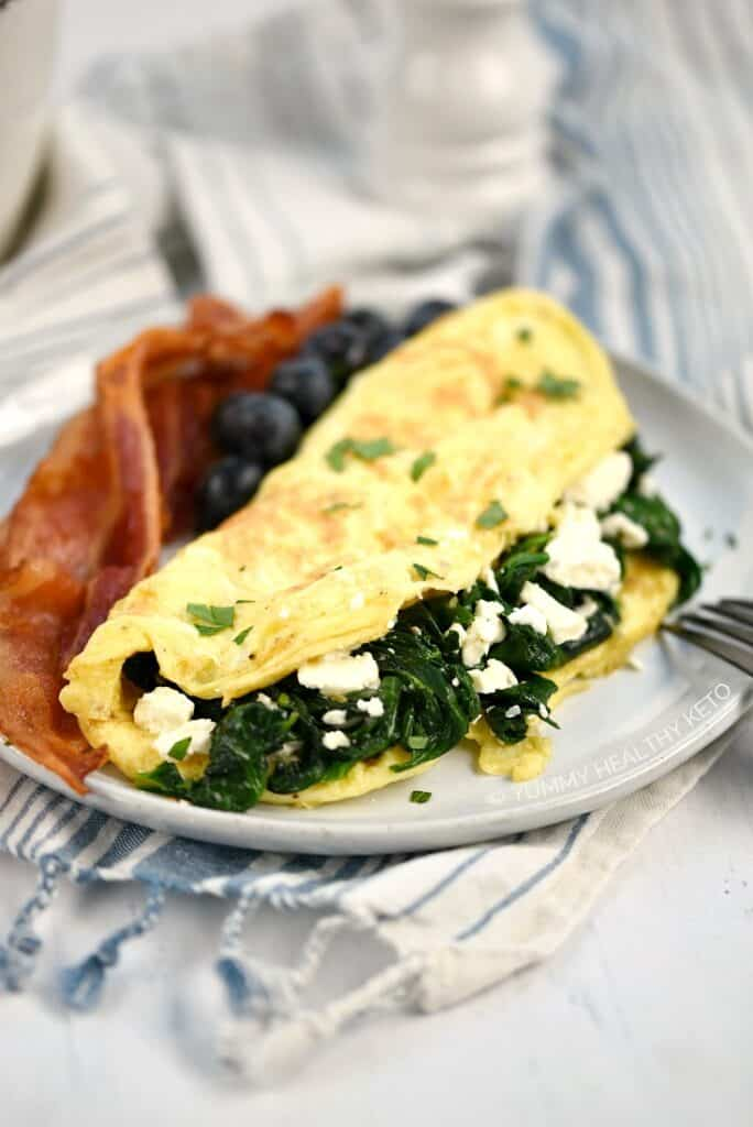 A Spinach and Feta Omelette on a plate with bacon slices and blueberries