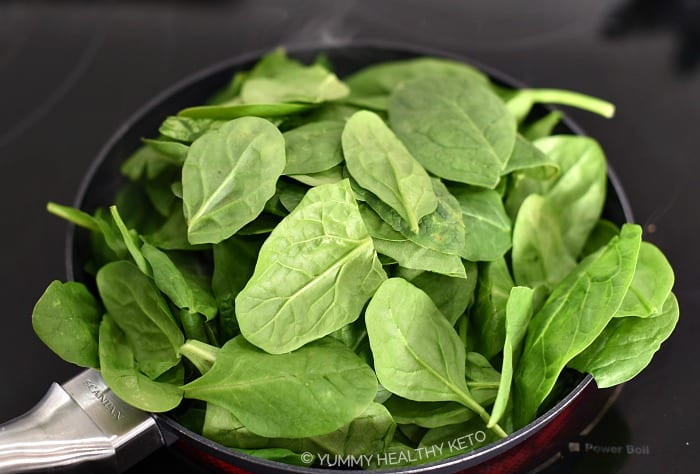 A pile of raw spinach in a small frying pan.