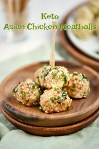 Five Keto Asian Chicken Meatballs stacked on a small wooden plate with a toothpick sticking out of the top and name graphic