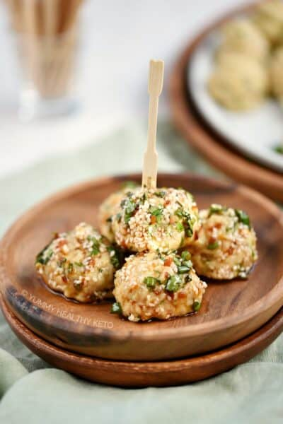 Five Keto Asian Chicken Meatballs piled on a small wooden plate with a toothpick sticking out of the top.