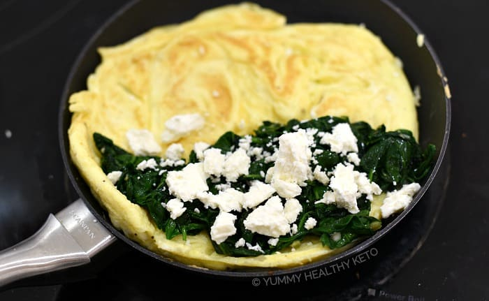 The cooked spinach and crumbled feta on one side of the egg circle.