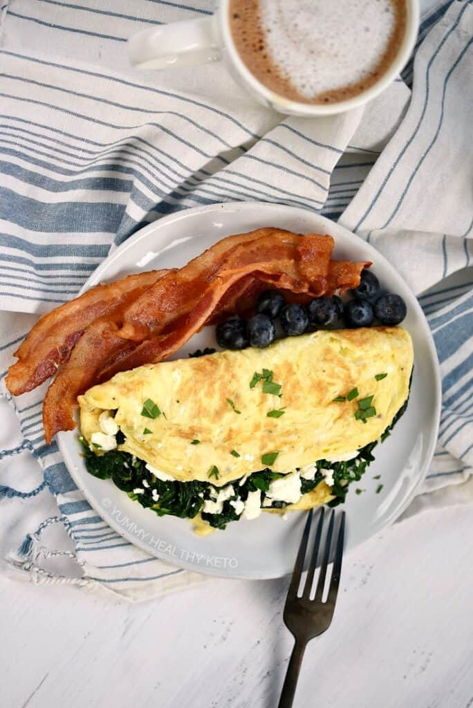 Looking down on a Spinach and Feta Omelette with three slices of bacon and a handful of fresh blueberries on a small plate